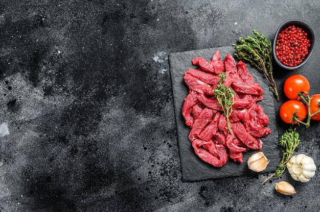 Viande crue coupée en fines lanières de boeuf stroganoff sur table noire.