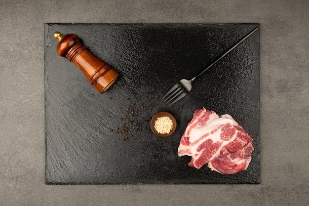 Viande crue et couteau à fourchette et sel et poivre sur une plaque de pierre noire