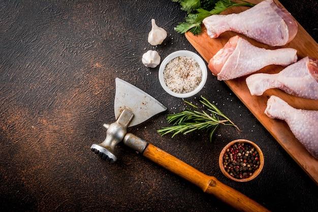 Viande crue, cuisses de poulet, aux herbes et épices n fond rouillé foncé, copie espace vue de dessus