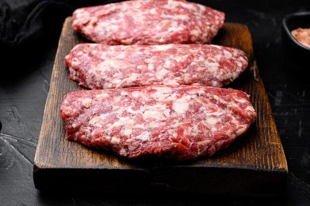 Viande crue, ensemble de côtelettes, sur fond de table en pierre noire noire