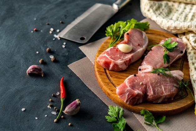 De la viande crue épicée sur une planche à découper en bois ou à découper, mettez du sel sur une viande non cuite