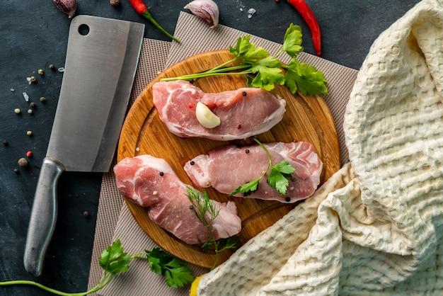 Viande crue épicée sur une planche à découper ou à trancher en bois, mettre un sel sur une viande non cuite