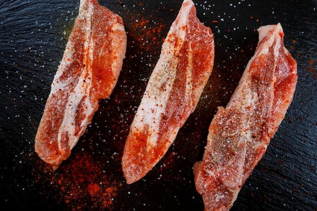 Viande crue sur fond sombre. steak de porc cru aux herbes, huile et épices. cuisson de la viande.