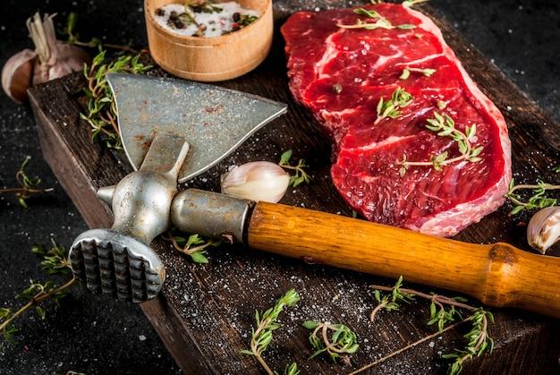 Viande crue fraîche boeuf morceau de filet de boeuf avec hache pour couper et hacher les épices de viande cuisinaient - ail sel de poivre de thym sur une vieille planche de bois sur un tableau noir en pierre