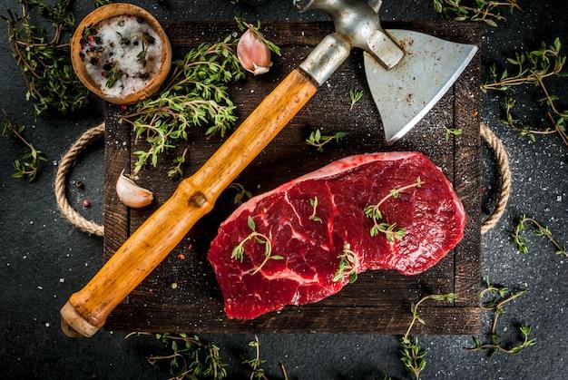 Viande crue fraîche boeuf un morceau de filet de boeuf avec une hache pour couper et hacher les épices de viande cuisinaient - poivre de thym sel ail