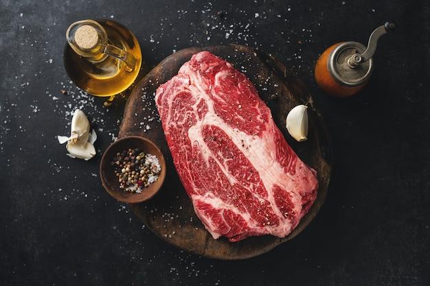 Viande crue fraîche avec des épices et du sel sur rustique foncé.