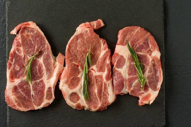 Viande crue fraîche avec épices et romarin et poivron rouge sur ardoise noire, sur fond sombre, porc, boeuf, surlonge boneles.