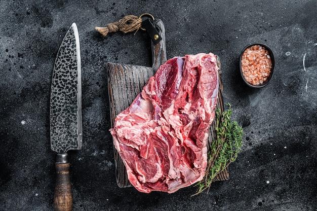 Viande crue de gigot d'agneau désossé sur une planche à découper en bois