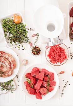 Viande crue hachée. le processus de préparation de la farine au moyen d'un hachoir à viande. saucisse maison. le bœuf haché. vue de dessus