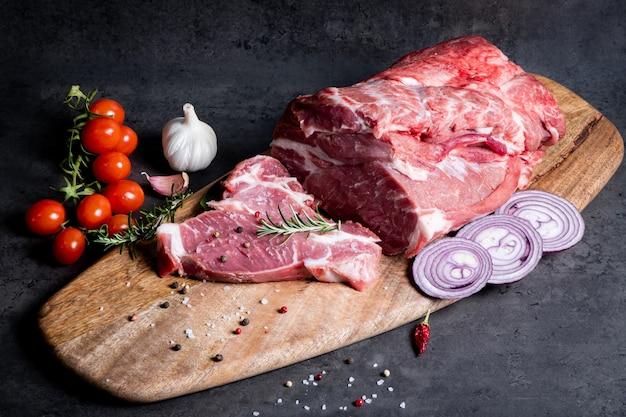Viande crue et légumes sur une planche à découper sur fond de ciment foncé