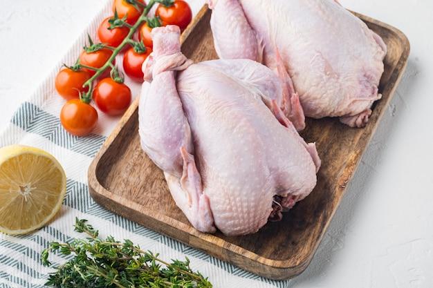 Viande crue de poulets coquelets aux herbes et ingrédients, sur fond blanc