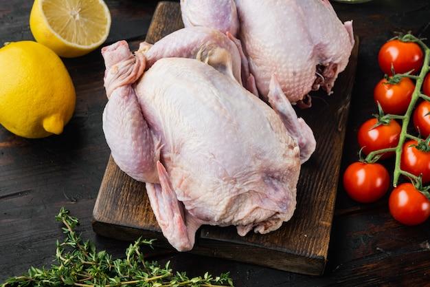 Viande crue de poulets coquelets avec des ingrédients sur une vieille table en bois
