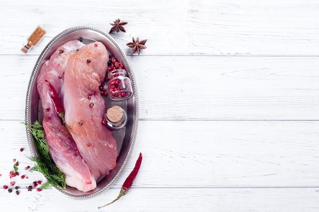Viande crue pour le gril, le barbecue ou la cuisine avec des herbes et des épices sur un plateau de fer