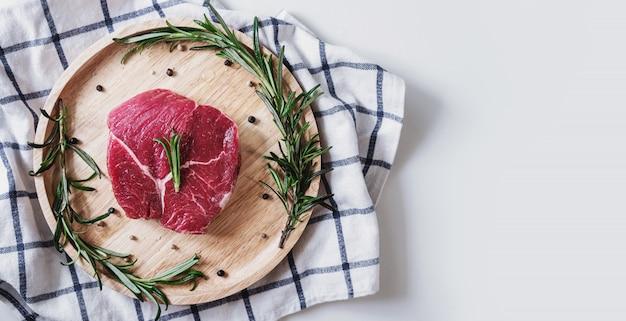Viande crue, steak de boeuf, sur planche de bois au romarin