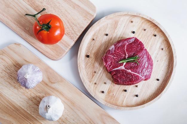 Viande crue, steak de boeuf, sur planche de bois avec tomate et ail. vue de dessus