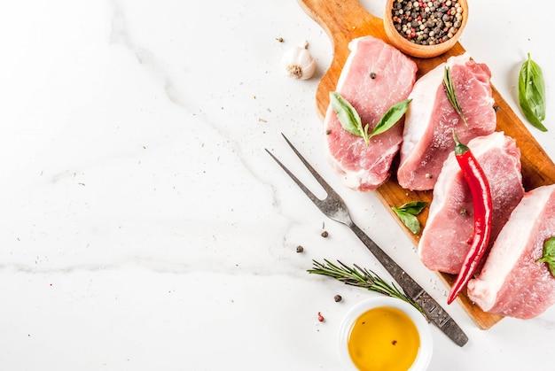 Viande crue, steaks de porc aux épices, fines herbes, huile d'olive