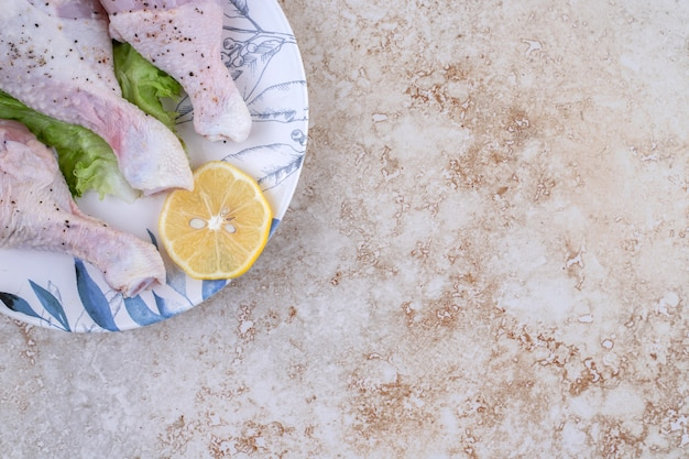 Viande de cuisses de poulet non cuites avec laitue et citron