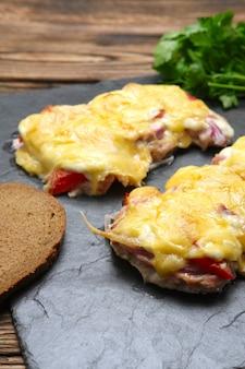 Viande cuite au four avec champignons, tomate et fromage, servet sur plaque de pierre
