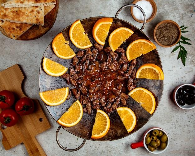 Viande cuite sur un saj et tranches d'orange en tranches