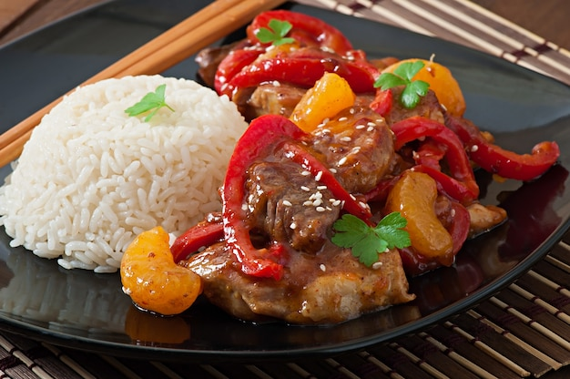 Viande dans une sauce épicée, poivron et mandarines avec une garniture de riz bouilli