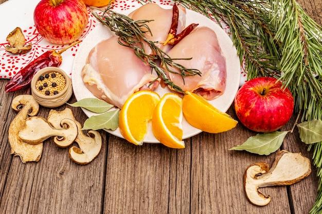 Viande désossée de poulet cru aux herbes et fruits sur la plaque. cuisine au jour de thanksgiving