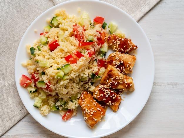 Viande de dinde, frite, avec sauce teriyaki et graines de sésame. couscous aux légumes.