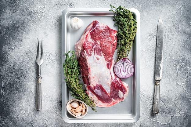 Viande d'épaule d'agneau ou de chèvre crue dans un plat allant au four avec couteau et fourchette à viande.