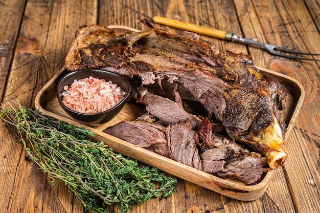 Viande d'épaule de coupe de mouton d'agneau rôti dans un plateau en bois avec fourchette à viande