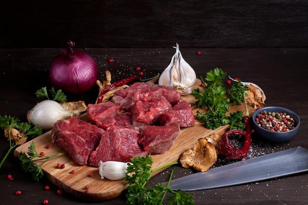 Viande fraîche crue; bouteille de vin et légumes bio d'automne sur planche de bois prêt pour la cuisson