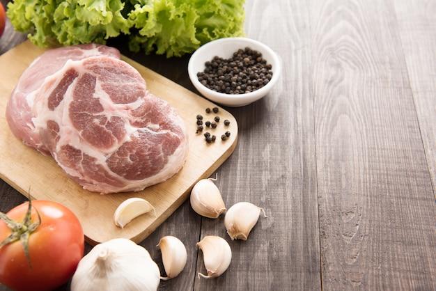 Viande fraîche crue et légumes sur table en bois