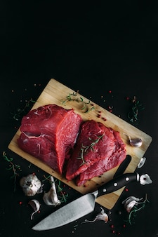 Viande fraîche et crue. morceau de boeuf rouge prêt à cuire sur le gril ou le barbecue