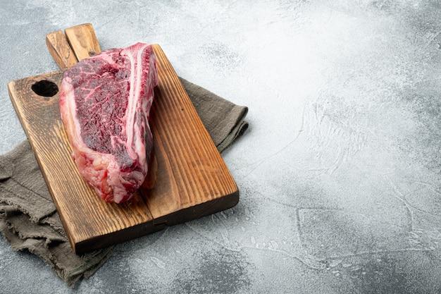 Viande fraîche crue à sec club steak set, sur table en pierre grise