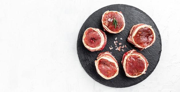 Viande fraîche crue steak filet mignon enveloppé de bacon et de thym sur fond blanc. format de bannière longue, vue de dessus.