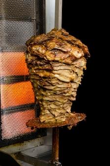 Viande fraîche de gyros grecs rôtir sur un bâton. isolé sur fond noir