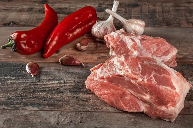 Viande fraîche avec des ingrédients pour cuisiner sur table en bois