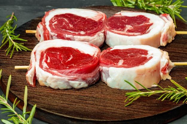 Viande fraîche avec des ingrédients pour la cuisson sur fond sombre, close up