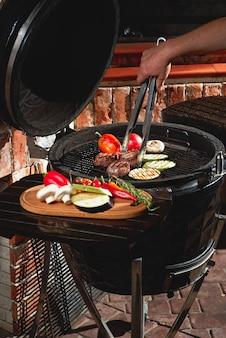 Viande fraîche et légumes grillés lors d'un barbecue fait maison le week-end. concept de cuisine, cuisine sombre.