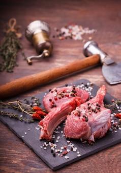 Viande fraîche sur le steak d'os avec des épices et des herbes