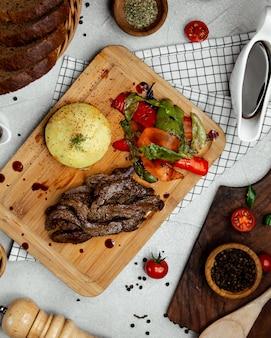 Viande frite aux légumes sur planche de bois