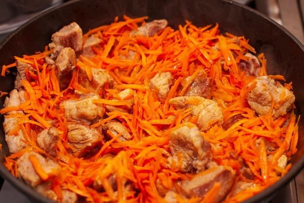 Viande frite avec des carottes dans une poêle. photo de haute qualité
