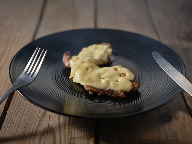 Viande frite avec du fromage sur une assiette