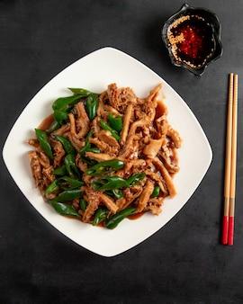Viande frite avec piment vert sur plaque