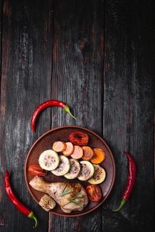 Viande frite sur une table en bois, cuisses de poulet savoureuses et juteuses, piments rouges chauds, place pour le texte