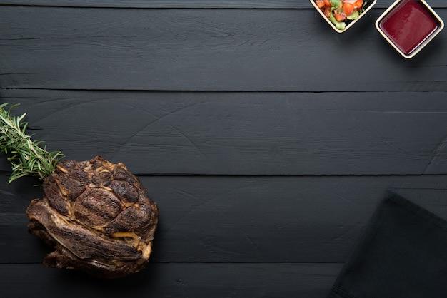 Viande frite avec des verts, de la sauce et de la sauce sur un fond en bois noir