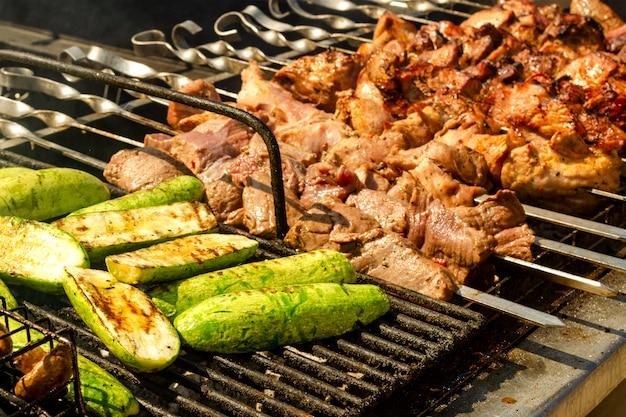 Viande sur le gril ou shish kebab et légumes pour la cuisson. frit sur des brochettes sur du charbon de bois chaud.