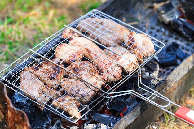 Viande grillée au barbecue avec des flammes et des charbons