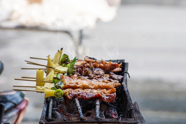 Viande grillée au barbecue avec des légumes et des sauces tomates sur les grilles en acier avec la chaleur.