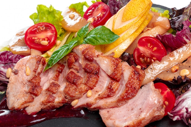 Viande grillée: boeuf (agneau) garnie de tomates, laitue