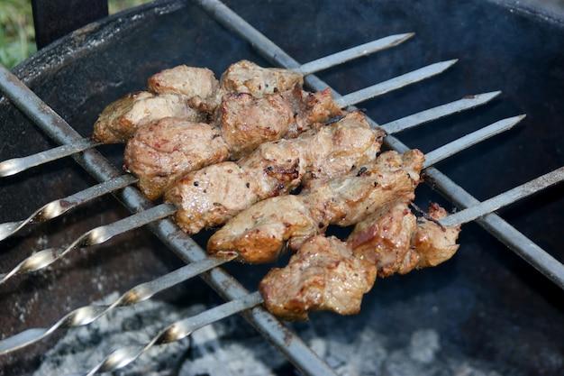 Viande grillée sur des brochettes sur charbon de bois