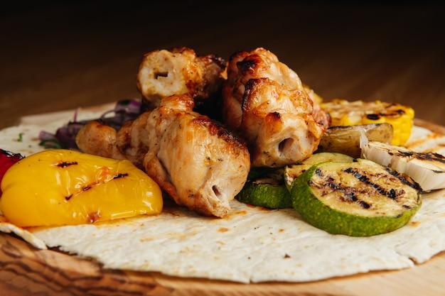 Viande grillée sur brochettes, shish kebab avec légumes sur planche de bois. poulet shashlik.